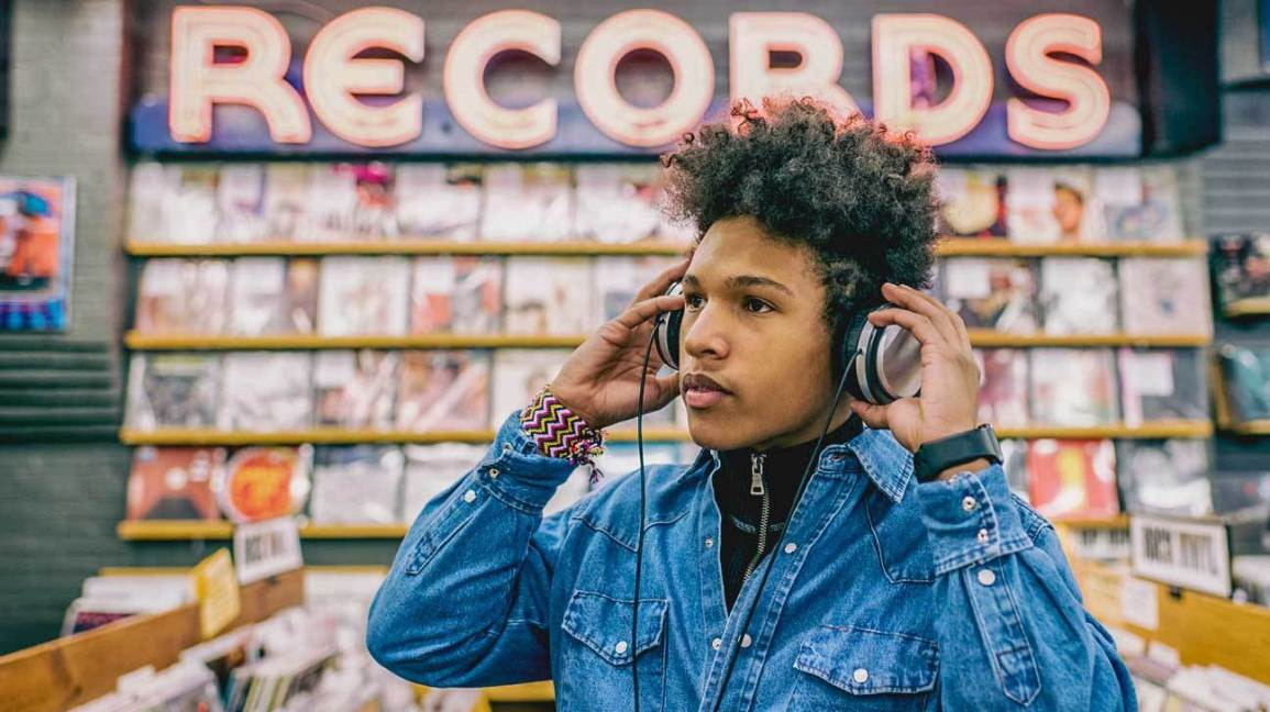 Teenage boy in record store listening to music